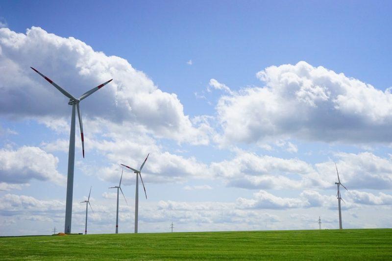 Veld met windmolens op een groene weide met een bewolkte lucht