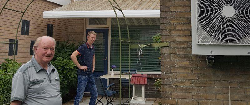 Joop Harmsen toont zijn warmtepomp. Installateur Robert Doornink kijkt toe.